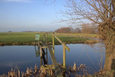 Over dit eenvoudige houten bruggetje kun je in buurtschap Teckop de wetering oversteken. (© Jan Dijkstra, Houten)