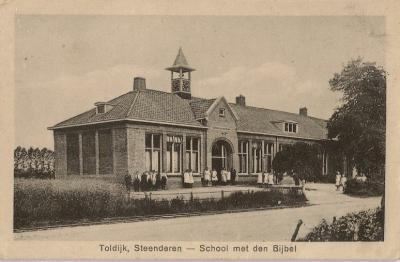 Sinds 1872 is er een lagere school in Toldijk, tegenwoordig basisschool De Rank geheten, vanouds de 'School met den Bijbel', hier afgebeeld op een ansichtkaart uit ca. 1920.