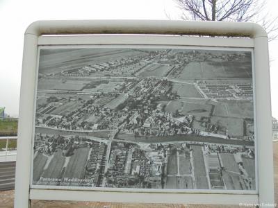 Historisch Genootschap Waddinxveen heeft op diverse markante plekken in het dorp zogeheten vertelbanken geplaatst, met een of meer fotopanelen, waarop de vroegere situatie ter plekke getoond wordt. Dit is er een van, met een foto van het dorp anno ca 1960
