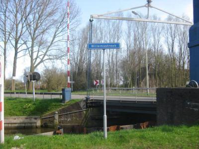 Buurtschap Willemsstreek heeft geen plaatsnaambordjes, maar gelukkig wel een gelijknamige weg, zodat je aan het straatnaambordje tenminste nog kunt zien dat je er bent aangekomen. Op de achtergrond de rijksmonumentale ophaalbrug. (© H.W. Fluks)