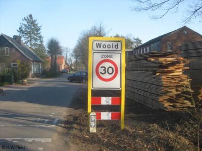 In de kern van Woold (die kennelijk formeel geen 'bebouwde kom' is anders waren het blauwe borden geweest) staan opnieuw plaatsnaamborden, met 30 km-zone