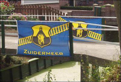 Zuidermeer heeft een dorpsvlag, met als symbolen de markante kerk, een melkbus en spoorrails, gezien de ligging aan de spoorlijn tussen Hoorn en Heerhugowaard. (© https://ximaar.wordpress.com)