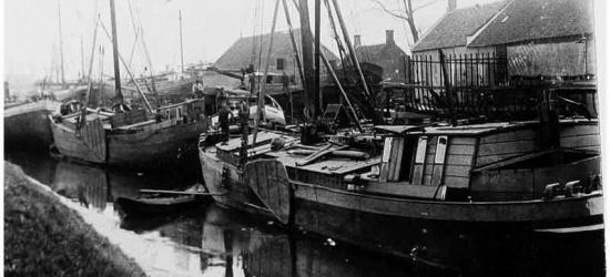 De Kerkvaartse Haven te Scharlo bij Waspik in 1900, gezien vanaf de kade naar het westen. Op de achtergrond de buurtschap Scharlo met in het midden de timmerloods van de scheepswerf van Ruijtenberg, daarnaast het woonhuis van Adriaan Ruijtenberg.