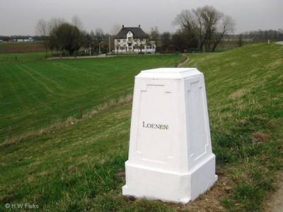 Loenen heeft geen plaatsnaambord, maar een 'plaatsnaamsteen'. Het is een 19e-eeuwse, rijksmonumentale grenspaal. Op de achtergrond de 19e-eeuwse opvolger van het Huis te Loenen.