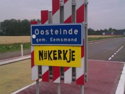 Oosteinde, plaatsnaambord, met daaronder een door de inwoners vervaardigd bord met de volksmondnaam van het dorp. Kennelijk een tijdelijk bord, want volgens ons staat dat bord er nu niet meer bij.