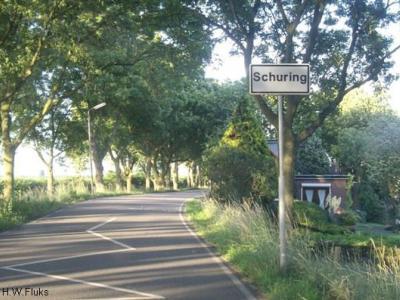 Buurtschap Schuring valt onder het dorp Numansdorp, ligt buiten de bebouwde kom en heeft daarom witte plaatsnaamborden