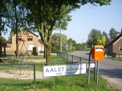 Toen buurtschap Aalst bij Lienden een bebouwde kom kreeg, en daarmee blauwe plaatsnaamborden, is een van de oude, witte plaatsnaamborden als aandenken opgehangen bij de speeltuin in de buurtschap. (© H.W. Fluks)