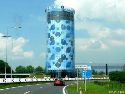 Vanaf afrit 2 aan de A2 kom je wel het grondgebied van Amsterdam binnen, maar nog niet de bebouwde kom. Die ligt een stukje verderop. Daarom is dit bord wit en niet blauw.
