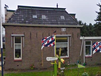 Zo te zien worden nieuwe inwoners in Bantega hartelijk verwelkomd met een versierde tuin, met daarin o.a. een fraaie vlag 'Wolkom yn Bantegea'. Dit is althans wat de Google-fotograaf aantrof op de hoek Middenweg/Bandsloot in nov. 2010. (© Google)