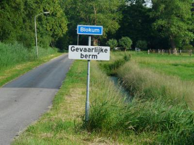 De buurtschap Blokum heeft geen plaatsnaambord, en dat hoeft ook niet met een gelijknamig straatnaambordje, mits het, zoals hier, haaks op de weg is geplaatst. Zo kan het als 2-in-1, straatnaambordje en plaatsnaambordje tegelijk, fungeren. (© H.W. Fluks)