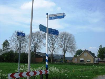 Twee bordmatige fouten in de buurtschap Hogeweg: de buurtschap heeft, in tegenstelling tot zusterbuurtschappen De Zande en Zuideinde, geen plaatsnaamborden, en op de richtingborden staat de plaatsnaam zwart op wit i.p.v. wit op blauw.