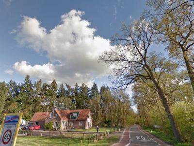 Op deze foto is goed te zien dat als je de bebouwde kom van de dorpskern van Hoenderloo, gem. Apeldoorn uitrijdt, je gelijk de buurtschap Hoog Baarlo 'in' Hoenderloo, gem. Ede binnenkomt (het witte plaatsnaambord verderop is Hoog Baarlo) (© Google)