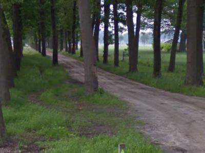 De buurtschap Kinderbos heeft geen plaatsnaamborden, zodat je slechts aan het gelijknamige straatnaambordje kunt zien dat je er bent aangekomen. De zandweg is de Jacob Reutenlaan, genoemd naar degene die in 1925 landgoed Kinderbos heeft gekocht. (©Google)