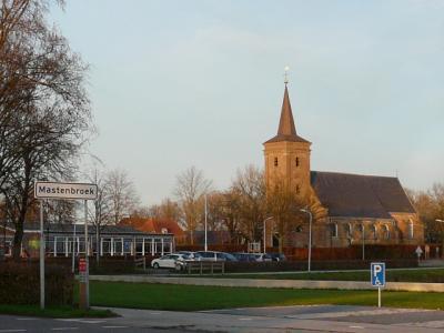 Het dorp Mastenbroek is zodanig dun en verspreid bebouwd dat het geen 'bebouwde kom' heeft. Vandaar witte plaatsnaamborden i.p.v. blauwe. Op de achtergrond de van oorsprong middeleeuwse kerk met toren uit 1845. (© H.W. Fluks)