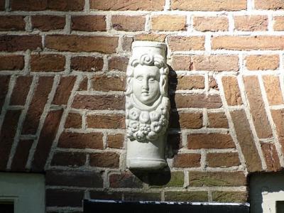 Een van de weinige overblijfselen van de borg Rheebruggen: een keramisch ornament, vermoedelijk afkomstig van een schouw uit de 17e eeuw en ingemetseld in de voorgevel van een boerderij op het gelijknamige landgoed. (© https://groninganus.wordpress.com)