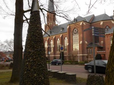 Vasse, de HH Jozef en Pancratiuskerk, met op de voorgrond een kunstwerk bij het Toeristisch Overstappunt (TOP)