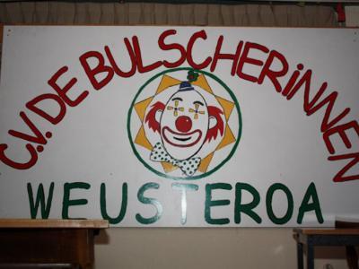 Natuurlijk doen ze ook in buurtschap Weustenrade aan carnaval. Bovenin de afbeelding kun je zien hoe de lokale carnavalsvereniging heet (genoemd naar het dorpscafé), onderin kun je zien hoe de plaats in het Limburgs heet (althans volgens de inwoners).