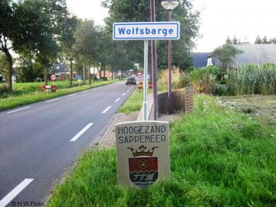 De buurtschap Wolfsbarge heeft witte plaatsnaamborden en ligt buiten de bebouwde kom (60 km-zone). Aan de Drentse kant, als je vanuit het Drentse dorp De Groeve Wolfsbarge binnenkomt, staat tevens een fraaie steen met het wapen van Hoogezand-Sappemeer.